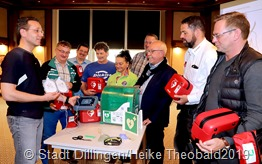 Marc Schneider (links) zeigt den Vertreter der Fußballvereine, den städtischen Mitarbeiter und Bürgermeister Franz-Josef Berg den Umgang mit den Defibrillatoren. Foto: Stadt Dillingen/Theobald