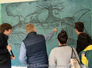 Schüler des Vorkurses 5 präsentieren Landrat Patrik Lauer die gemeinsame Arbeit mit der Künstlerin Lioba Amann im Pausenhof der Schule.