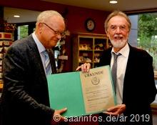 Bürgermeister Lothar  Christ ( r) überreicht die Urkunde