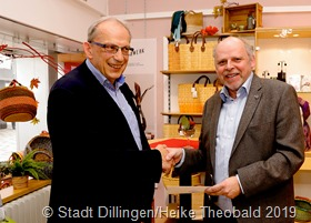 Der 1. Beigeordnete Stefan Schmitt gratuliert dem VHS-Leiter Stefan Dewes zum 10. Jubiläum des Fairen Ladens.