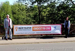 An drei Verkehrsknotenpunkten in Saarlouis weisen die Banner auf das Hilfetelefon hin, darunter eines in der Eisenhüttenstädter Alle, das OB Peter Demmer und Frauenbeauftragte Sigrid Gehl präsentieren. Foto: Sascha Schmidt