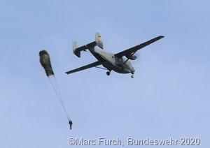 Ein Automatik-Fallschirmspringer der Luftlandebrigade 1 kurz nach Verlassen des Flugzeugs. Der Schirm des Fallschirmjägers kurz vor seiner vollständigen Entfaltung.