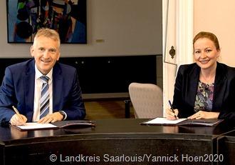 Ministerin Streichert-Clivot und Landrat Patrik Lauer bei der Vertragsunterzeichnung.