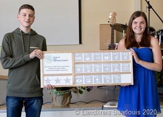 """Foto: Landkreis Saarlouis/Nadine Niewel - Schüler präsentieren stellvertretend für die Schule die Auszeichnung zur """"Schule der Nachhaltigkei"""