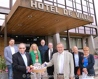 Der Erste Beigeordnete Stefan Schmitt(links) überreicht Bürgermeister Jean-Luc Wozniak im Beisein einiger Beigeordneter einen Korb voller Blumengrüße. Foto: Stadt Dillingen/Theobald